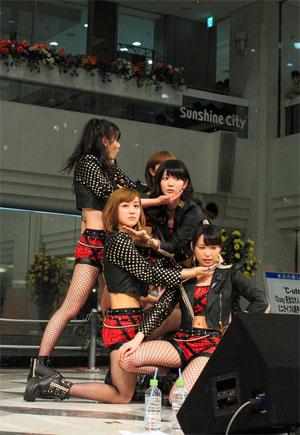 A C-ute csapat az Ikebukuro Sunshine City-ben a Crazy Kanzen na Otona előadására készül, a 2013-as Nippon Budokan koncert bejelentése előtti pillanatokban.